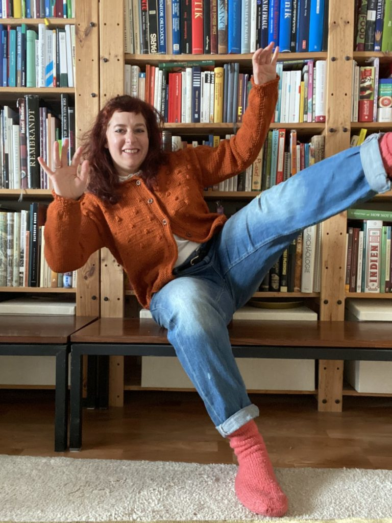 woman wearing a orange colored hand knitted Rönn cardigan in forn of a huge book shelf