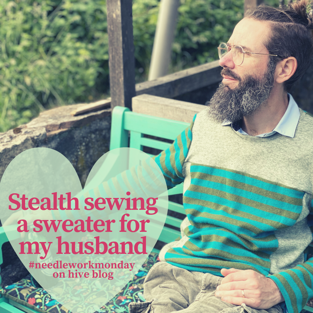a bearded man wearing a handmade striped sweater in a garden